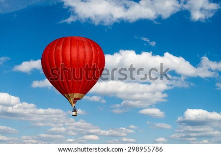 Red hot air balloon in blue cloudy sky