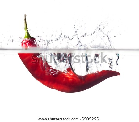 Red hot chili pepper splashing into water isolated on white