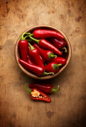 Red Hot Chili Peppers in bowl over wooden background