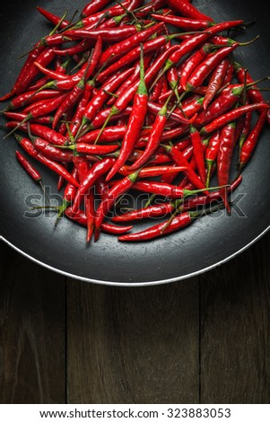 Red Hot Chili Peppers in old pan on rusty steel  background, Still life photography with overhead view of chili pepper on wood background, Dark mood of food photography with red chili peppers
