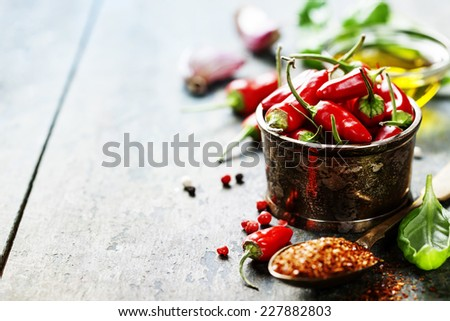 Red Hot Chili Peppers with herbs and spices over wooden background - cooking or spicy food concept #227882803