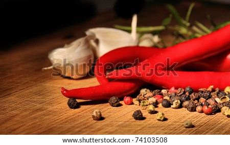 Red hot chili peppers with spice ingredients over wooden background - stock photo
