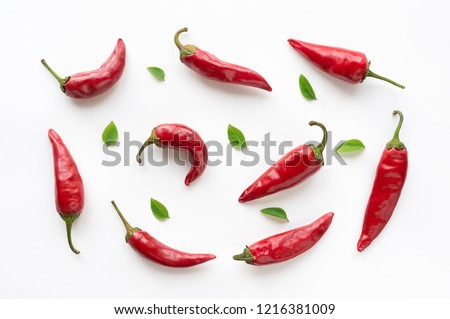 Red hot chilli peppers with green leaves on white background. Food pattern.