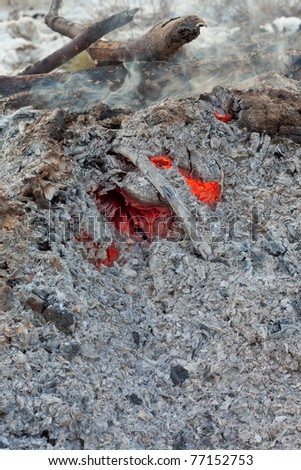 Red-hot coals still glowing and smoking under heap of ashes left from wood burning bonfire.