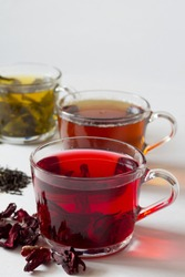 Red hot Hibiscus tea with dry flowers. Healthy lifestyle.Three glass cups with black, red and green tea on a white background.  Green hot tea. Black hot tea. Hot drinks. Vertical orientation.