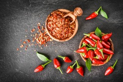 Red hot peppers in wooden bowl on dark stone table. Chili small pepper seeds in scoop and green leaves on black background top view.