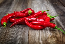 Red hot peppers on wooden background.