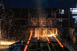 Red hot steel metal billets after molten steel casting.  Continuous casting machine. Background of the blacksmith and metallurgical industry.