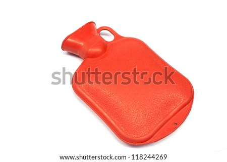 Red hot water bottle made of rubber in front of a white background