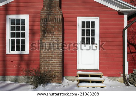 Red house, covered in snow, rural setting, suitable for winter, seasonal designs