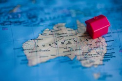 Red house model on Australia part of world map. Buying of real estate in / migration to Australia concept.