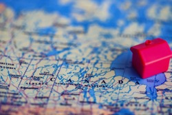 Red house model on Canada part of world map. Real estate buying in/ migration to Canada concept.