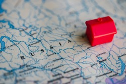 Red house model on Russia part of world map. Real estate in/ migration to Russia concept.