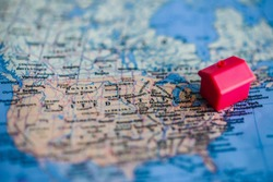 Red house model on United States (map). Residence/citizenship in/ immigration to United States concept.