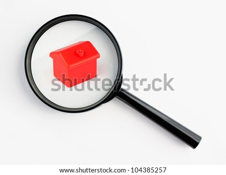 red house under a magnifying glass, with isolated background