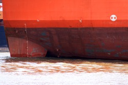 Red hull of a ship with display of the draft