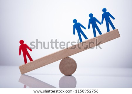 Red Human Figure Standing Against Blue Team On Wooden Seesaw