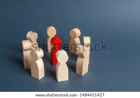 Red human figure surrounded by a circle of people. Leader Boss and leadership. Cooperation and teamwork. Outcast, hated opponent, criminal. Conviction. Discrimination and violence. Foto stock ©