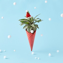 Red ice cream cone with pineapple on pastel blue background with snow ball. Creative minimal christmas concept