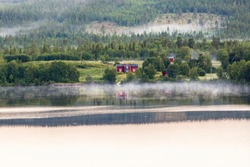 Red idyllic cottage in a forest lake and fog
