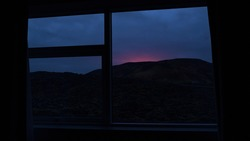 Red illuminated sky in the early morning after the eruption of a volcano near Fagradalsfjall, Reykjanes peninsula, Iceland viewed from a hotel room north of Grindavík on 2021-03-20.