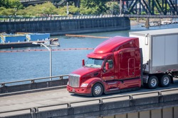Red industrial grade diesel big rig semi truck with low cab for best aerodynamics transporting commercial cargo in dry van semi trailer running along the river on overpass highway road intersection