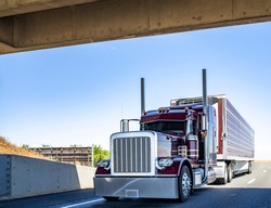 Red industrial long haul Big rig bonnet semi truck with chrome transporting frozen commercial cargo in refrigerator semi trailer running for delivery on wide multiline highway road under the bridge
