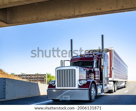 Red industrial long haul Big rig bonnet semi truck with chrome transporting frozen commercial cargo in refrigerator semi trailer running for delivery on wide multiline highway road under the bridge Сток-фото ©