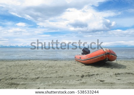 Red inflatable or rigid hulled boat on a alaskan beach  #538533244