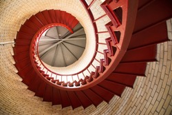 Red iron spiral staircase inside a lighthouse
