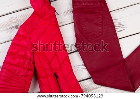 Red jacket and crimson pants. Folded clothes on wooden display. Bright garments for cold cloudy winter. #794053129