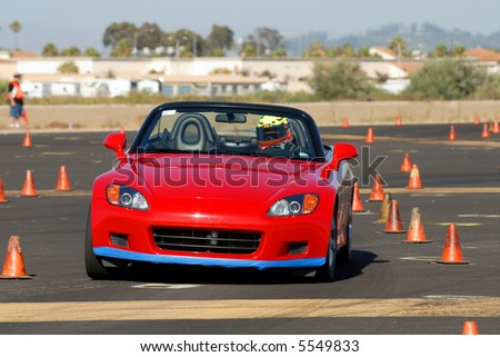 red Japanese sports car competing in auto cross race