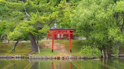 Red Japanese Temple Gate Surrounded by Trees