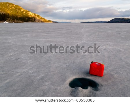 Red jerry-can full of gasoline on vast frozen Lake Laberge, Yukon Territory, Canada