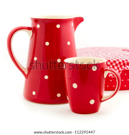 Red jug and cup on white background. Holiday tableware arrangement.