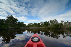 Red kayak in Coot Bay Pond in Everglades National Park, Florida under winter cloudscape reflected in tranquil water.