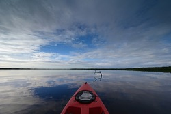 Red kayak on Coot Bay in Everglades National Park, Florida under winter cloudscape reflected in tranquil water,