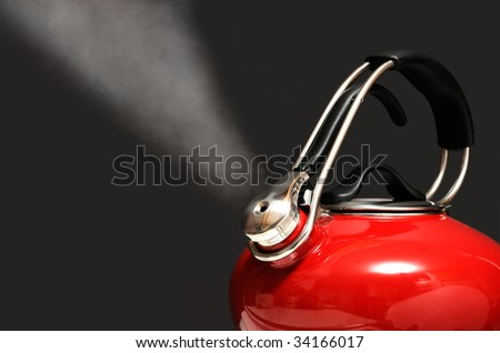 Red kettle boiling water isolated on black. Steam coming out.