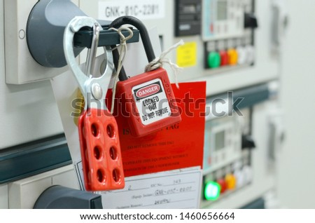 Red key lock and white tag for process cut off electrical on control panel in substation at chemical plants, power plants, oil & gas industry or onshore industry. isolation tag and do not remove tag. Foto stock ©
