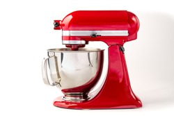 Red kitchen mixer with bowl on a white background and copy space.