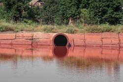 Red lake in a day with rust outgoing pipe. Settling basin of mine waters.