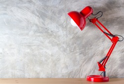 Red lamp on wooden desk in modern room, with copy space.