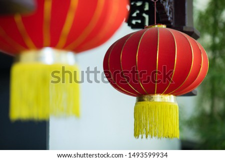 Red lantern hanging high at the entrance of the house