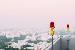 Red lantern of obstruction lights, mounted on the rooftop of high rise tall building to ensure flights safety and warn the danger for the plane, located against the background of the city, copy space