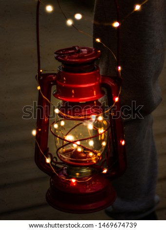red lantern with garland surrounding it in a dim environment