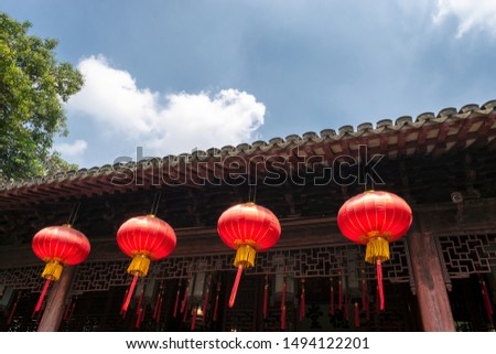 Red lanterns, symbols of vitality and good luck, hanging from the roof of old traditional style Chinese residence (Siheyuan)