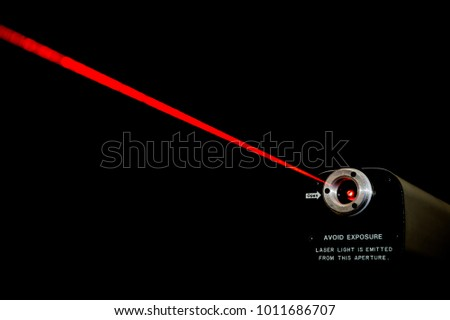 Red laser beam from a lab laser. Warning notice on front. Black background. #1011686707