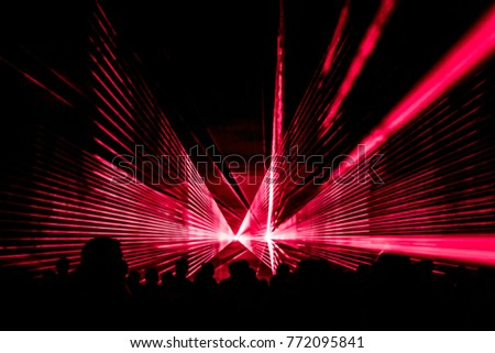 Red laser show nightlife club stage with party people crowd. Luxury entertainment with audience silhouettes in nightclub event, festival or New Year's Eve. Beams and rays shining colorful lights