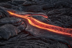 Red lava flow from black volcanic ground on melted dark background