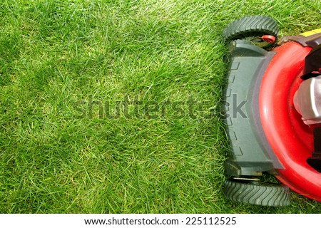 Red Lawn mower cutting grass. Gardening concept background #225112525